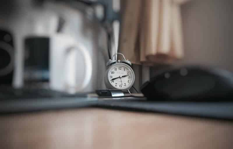 Blurred picture of a desk with a focus on a old time alarm clock